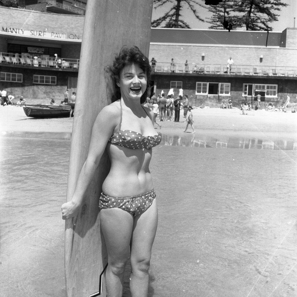 Girl wearing a polka dot bikini and holding a surfboard, Manly c.1957